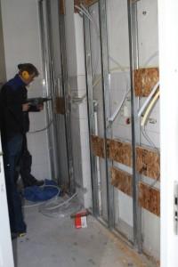 De keukenwand bleek te zwak voor het installatiewerk. Een metalstud voorzetwand bleek de oplossing.